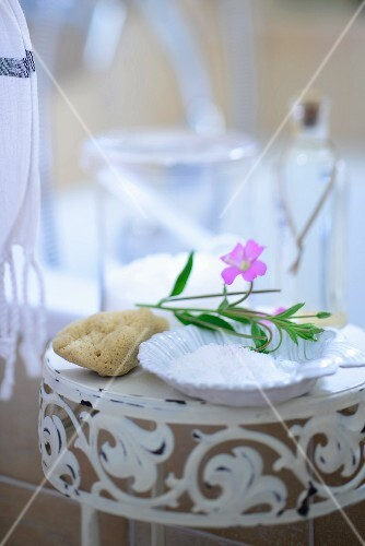 Bathing salts, a natural sponge and flowers on a side table in a bathroom
