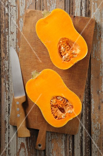 A halved butternut squash on a chopping board with a knife