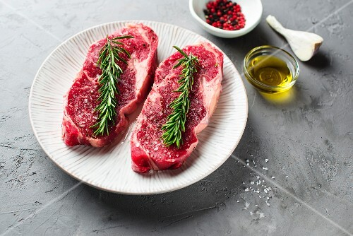 Raw beef steaks with rosemary and spices