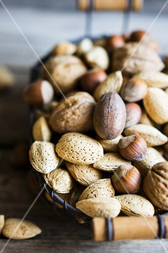 A nut mix in a basket on a rustic wooden surface