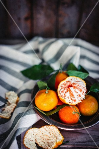 Mandarins with leaves in a metal bowl on a rustic wooden surface