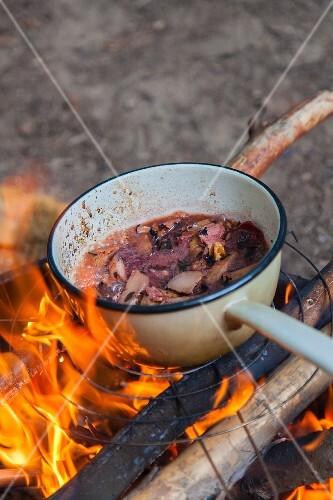 A saucepan of stew over a campfire