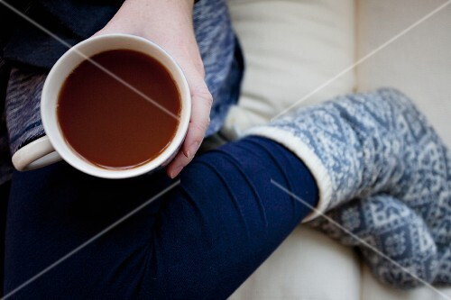 A woman sitting on a sofa with a cup of coffee and winter socks