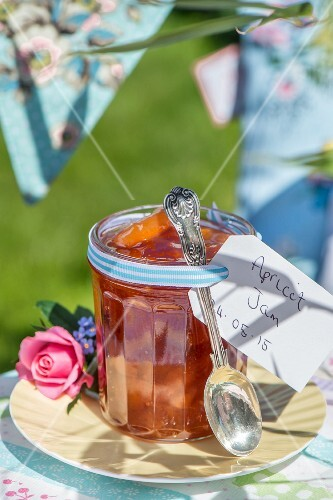 Homemade apricot jam in a jar on a table outside
