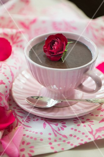 Chocolate pudding in a cup garnished with a rose