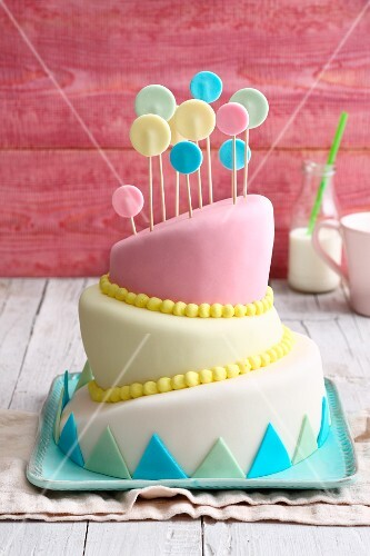 A slanted topsy-turvy cake decorated with pastel-coloured fondant icing