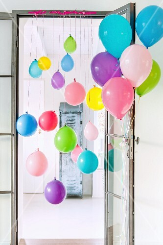Colourful balloons tied to door frame and door