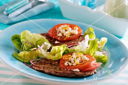 Steaks with tomatoes, feta cheese and lettuce