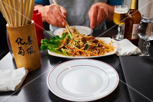 A person eating an Oriental noodle dish with chopsticks