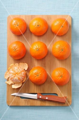 Whole mandarins and a peeled mandarin on a wooden board