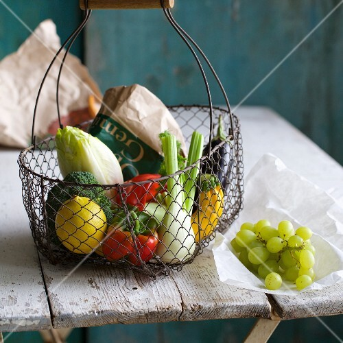 Vegetables and lemons in a shopping basket next to grapes on an old wooden table