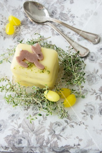 A petit four decorated with an Easter bunny, thyme and sugar eggs