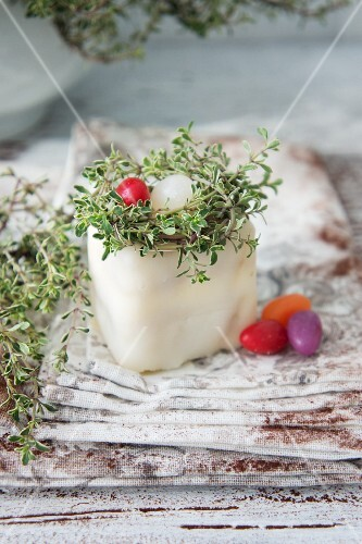 A petit four decorated with a nest, thyme and sugar eggs