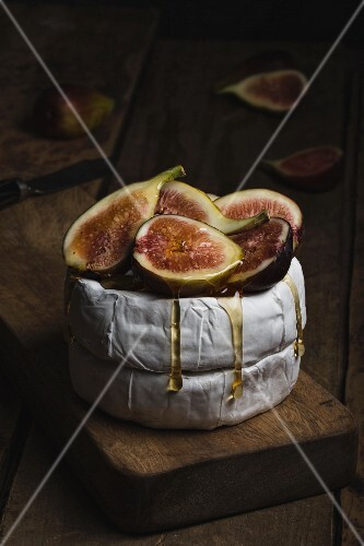 Camembert cheese with honey and fresh figs on wooden chopping board