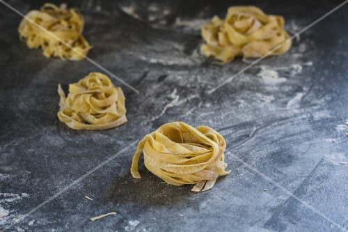 Homemade tagliatelle on a floured work surface