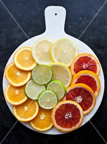 Lemon, lime, orange, and blood orange slices on a white tray (seen from above)