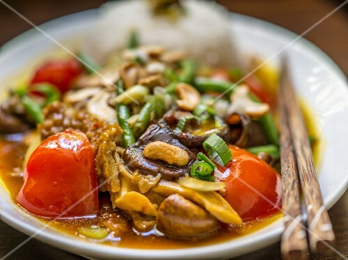 Chicken with mushrooms, cashew nuts, tomatoes, beans and a side of rice (Asia)