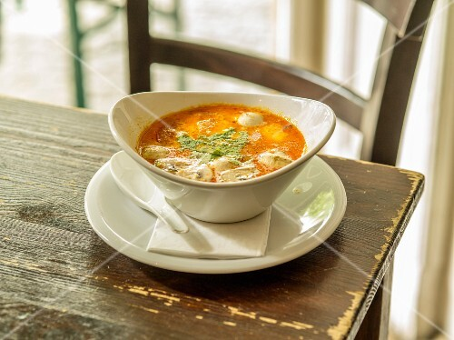 Spicy coconut milk soup with coriander, tomatoes, mushrooms and lemongrass