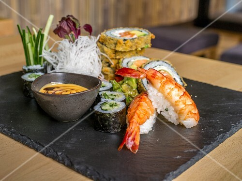 Various types of sushi on a slate platter in a restaurant