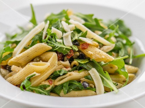 Pasta salad with rocket, dried tomatoes and Parmesan cheese (close-up)