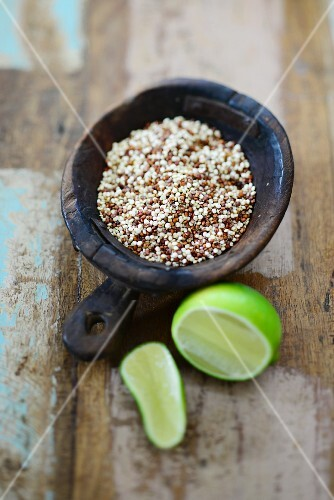 Coloured quinoa in a wooden bowl with a lime next to it