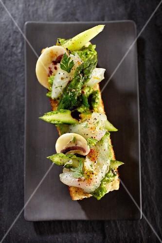 Seabream carpaccio on white bread with vegetables