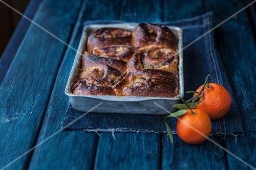 Apple and cinnamon buns in a baking dish next to mandarins