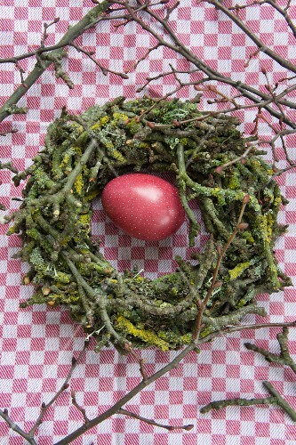Stone egg in Easter nest of apple tree twigs