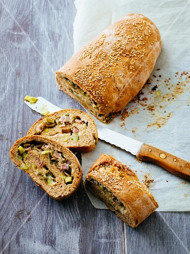 A bread roll filled with ham, cheese and courgette