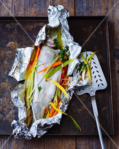 Trout with julienned vegetables in aluminium foil