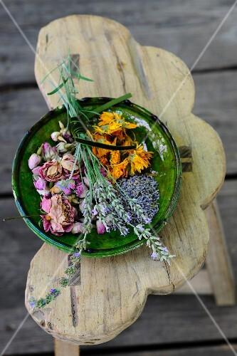 Dried medicinal herbs in a green ceramic bowl