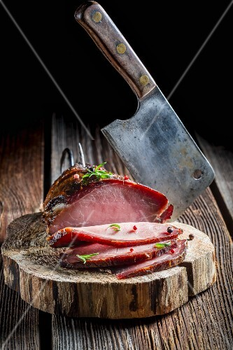 Smoked ham and a meat cleaver on a tree stump