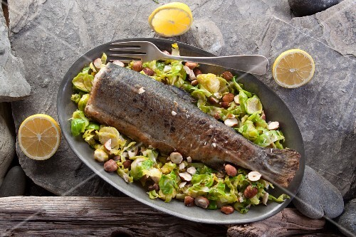 Fried trout on a bed of Brussels sprouts with hazelnuts