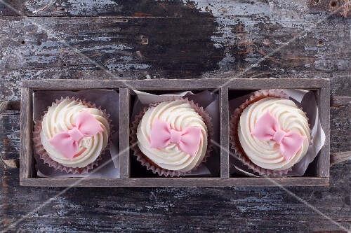 Cupcakes decorated with pink fondant bows (seen from above)