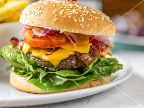A cheeseburger with tomatoes, onions and salad (close-up)