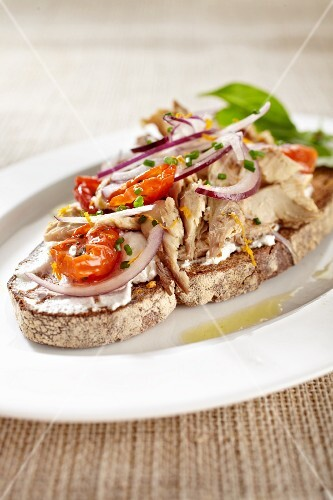 An open summer sandwich with tuna fish, tomatoes and red onions