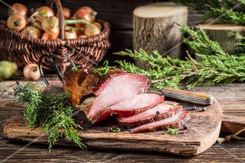 Smoked ham with juniper berries on a wooden chopping board