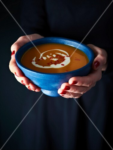 A woman holding a bowl of cream of pumpkin soup