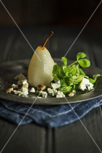 A poached pear with blue cheese and basil