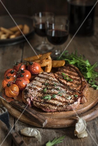 Grilled beef steak with tomatoes and chips on a wooden plate
