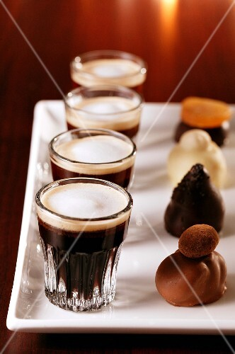 Pralines and black coffee with milk foam