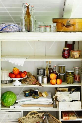 Preserving jars, kitchen utensils, vegetables and fruit in pantry