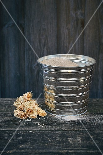 Waxed wood wool as a fire lighter and a sand bucket for extinguishing