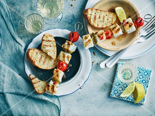 Grilled fish skewers with cherry tomatoes and baguette