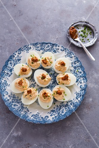 Devilled eggs with red pesto on a vintage plate