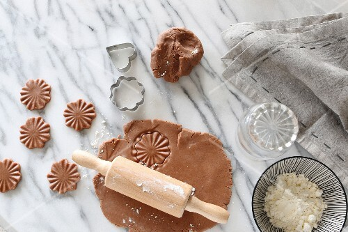 Gluten-free pastry rolled out with a rolling pin with cutters and a bowl of gluten-free flour on a marble surface