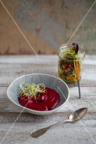 Creamy beetroot and coconut soup with onion sprouts and salad in a jar