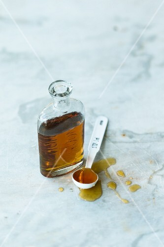 Maple syrup in a bottle and on a spoon