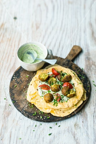 Curry falafel with corn tortillas with green sauce and sesame seeds