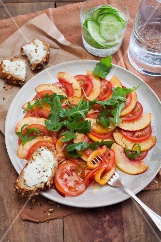 Nectarine and tomato carpaccio with goat's cream cheese on bread